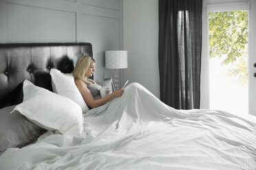 Woman reading with digital tablet in bed - HEROF20346