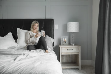 Woman relaxing, drinking coffee and texting with smart phone in bed - HEROF20349