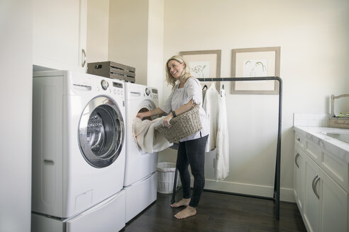 Woman removing laundry from dryer in laundry room - HEROF20358