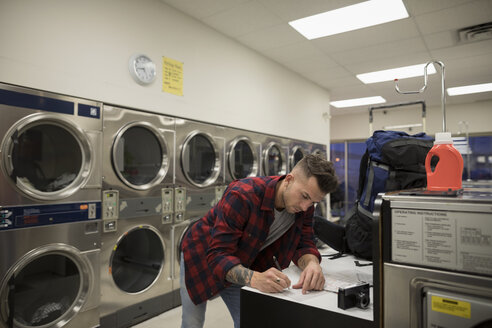 Young male backpacker writing letter waiting for laundry at laundromat - HEROF20382