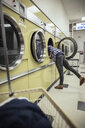 Young woman reaching in clothes dryer, doing laundry at laundromat - HEROF20385