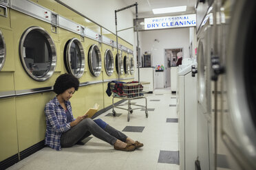Young woman reading book, waiting for laundry at laundromat - HEROF20388
