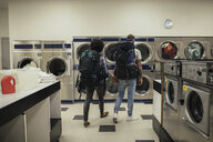 Young couple backpackers doing laundry at laundromat - HEROF20391