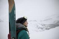 Thoughtful female skier enjoying snowy mountain view - HEROF20415