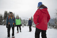 Woman leading snowshoeing tour for friends in snow - HEROF20421