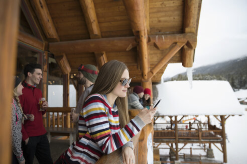 Young woman texting with smart phone apres-ski on snowy ski resort lodge balcony - HEROF20424