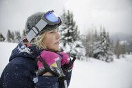 Thoughtful female skier looking away in snow - HEROF20439