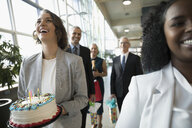 Laughing businesswoman carrying birthday cake in office - HEROF20472