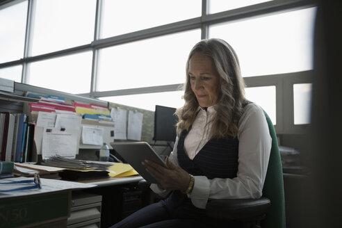 Focused mature businesswoman using digital tablet in office cubicle - HEROF20475