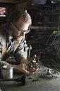 Focused male blacksmith examining pieces in blacksmith shop - HEROF20502