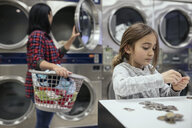 Girl counting coins, helping mother doing laundry at laundromat - HEROF20550