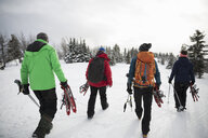 Friends carrying snowshoeing equipment in snow - HEROF20589