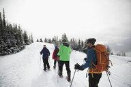 Friends snowshoeing in snow - HEROF20592