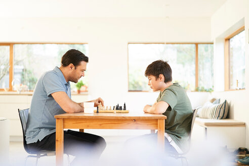 Boy and father playing chess at living room table - CUF48517