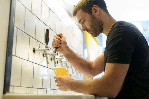 Brewer pouring beer in small brewery - CUF48544