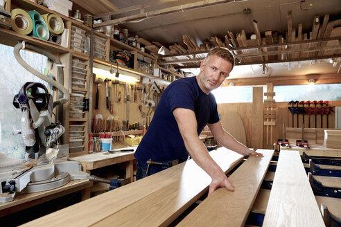 Craftsman preparing planks of wood in workshop - CUF48586
