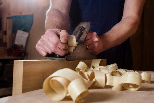 Craftsman using wood plane in workshop - CUF48595