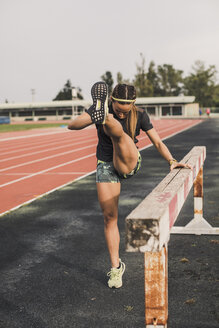 Female athlete doing warm-up exercises on tartan track - ACPF00440