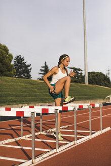 Female athlete doing warm-up exercises on tartan track - ACPF00443