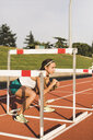 Female athlete doing warm-up exercises on tartan track - ACPF00446