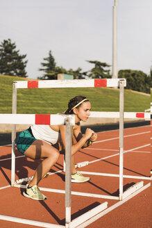 Female athlete doing warm-up exercises on tartan track - ACPF00446