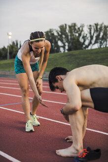 Male and female athlete on tartan track - ACPF00458