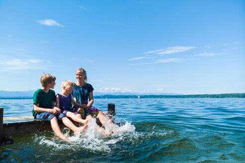 Mother and children cooling feet in water, Lake Starnberg, Bavaria, Germany - CUF48799