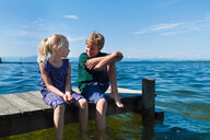 Siblings cooling feet in water, Lake Starnberg, Bavaria, Germany - CUF48820