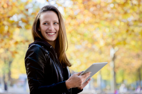 Young woman using digital tablet in park - CUF48823