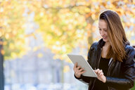 Young woman using digital tablet in park - CUF48826