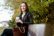 Young woman on coffee break in park - CUF48829