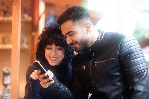 Couple using smartphone at Christmas market, Freiburg, Baden-Wurttemberg, Germany - CUF48835