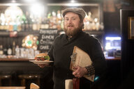 Man with plate of burger and menu in pub - CUF48937