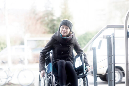 Woman in wheelchair moving up ramp - CUF48952