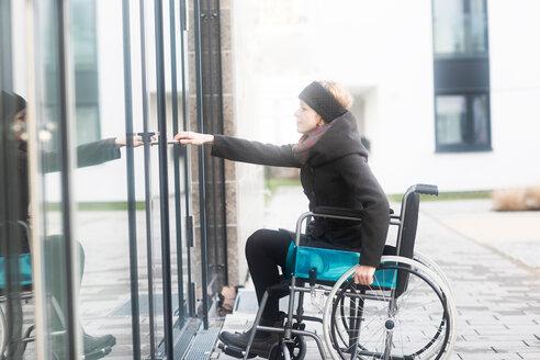 Woman in wheelchair opening door to building - CUF48958