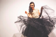 Woman holding tulle skirt dancing - CUF48991