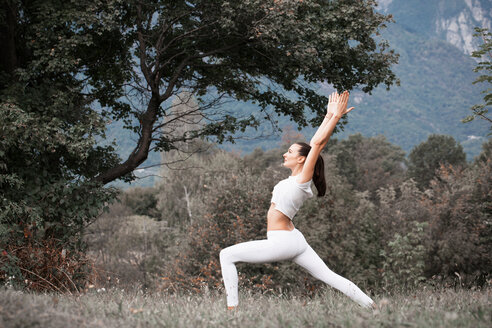 Woman practicing yoga, warrior pose in rural landscape - CUF49006
