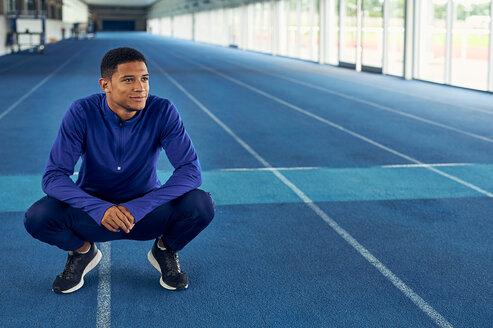 Runner resting on indoor running track - CUF49048