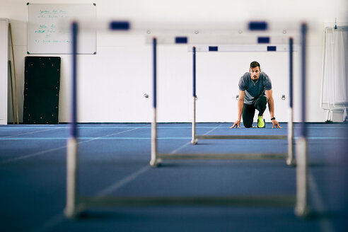 Athlete getting ready for hurdles on indoor running track - CUF49066