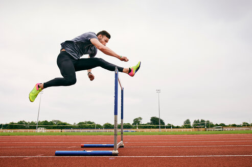 Athlete jumping over hurdle on running track - CUF49069
