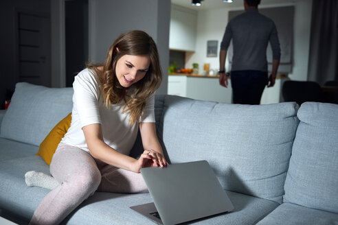 Young woman sitting on sofa in evening, peeking at boyfriend's laptop - CUF49108