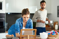 Couple drinking coffee and using digital tablet in kitchen - CUF49111