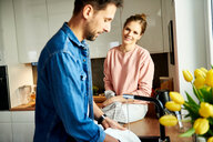 Couple talking and washing up in kitchen - CUF49129