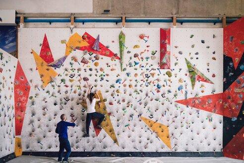 Climber guiding friend on climbing wall - CUF49135