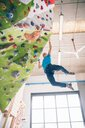 Climber dangling from climbing wall - CUF49141