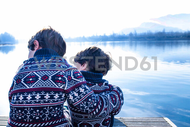 Boy and toddler brother in matching sweaters sitting on pier, Lake Como, Lecco, Lombardy, Italy - CUF49219 - Bonfanti Diego/Westend61