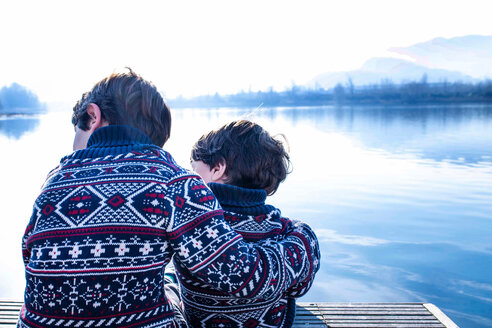 Boy and toddler brother in matching sweaters sitting on pier, Lake Como, Lecco, Lombardy, Italy - CUF49219