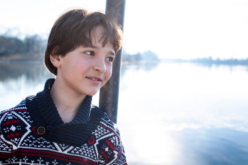 Boy leaning against lakeside post, portrait,  Lake Como, Lecco, Lombardy, Italy - CUF49222