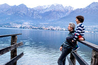 Boy and father looking out from lakeside pier, Lake Como, Onno, Lombardy, Italy - CUF49225