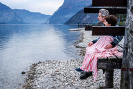 Boy and father wrapped in blanket on lakeside pier, side view, Lake Como, Onno, Lombardy, Italy - CUF49228